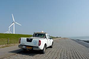 Jeep van waterschap Scheldestromen op zeewering met windmolens