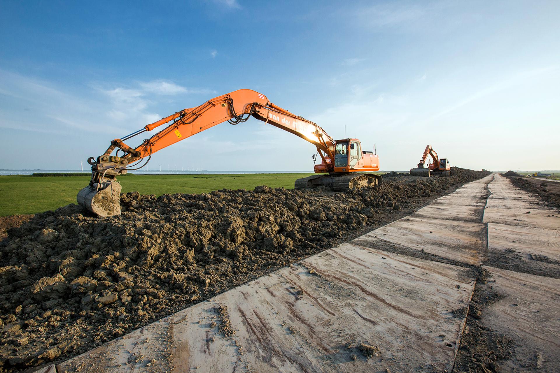 Dijkversterking in Friesland - graafmachine op de dijk