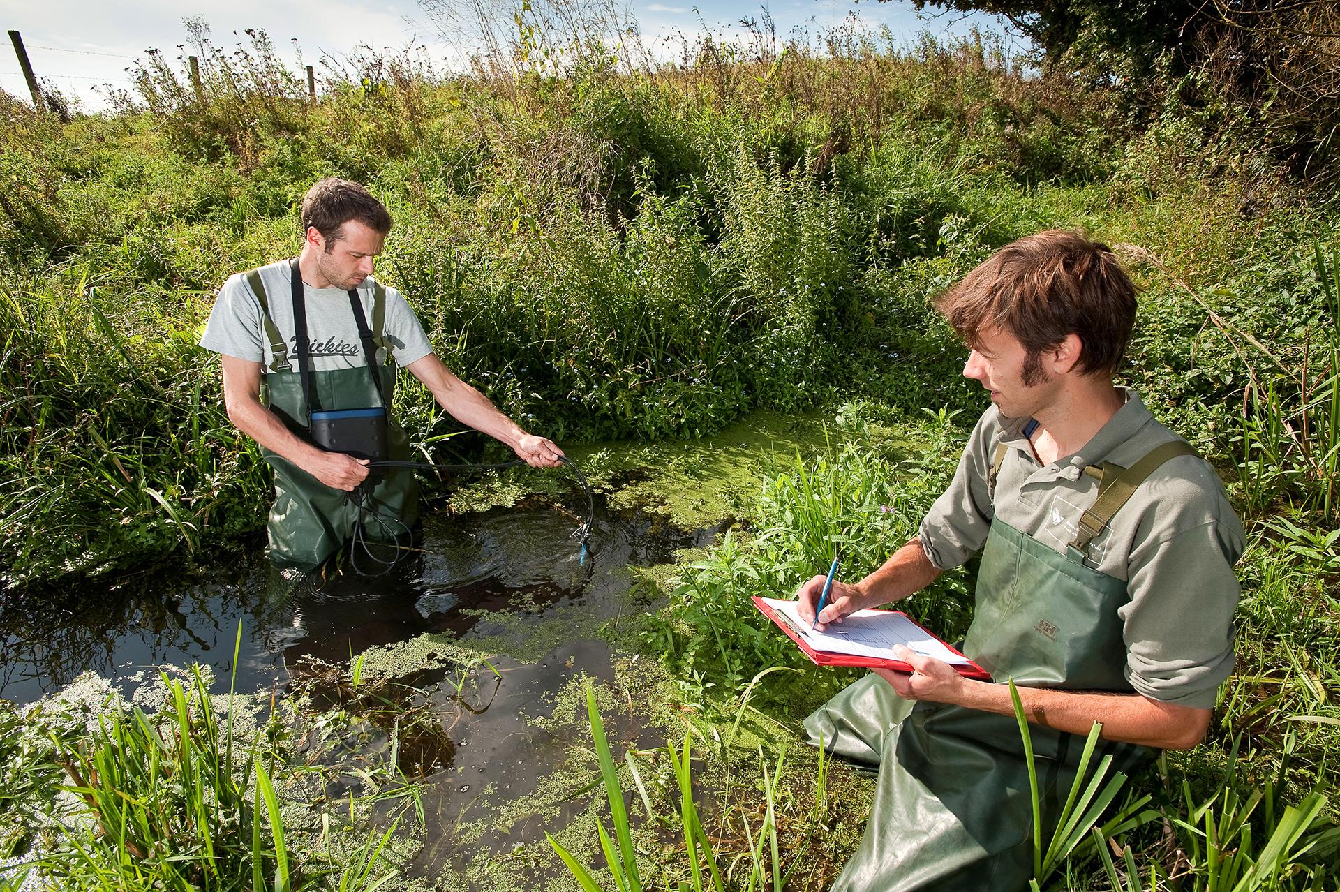 Twee waterschapsmedewerkers controleren de waterkwaliteit