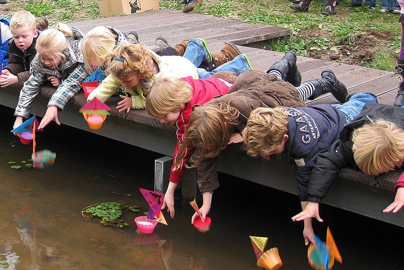 Waterdiertjesdag in waterschap Aa en Maas, kinderen laten papieren bootjes te water