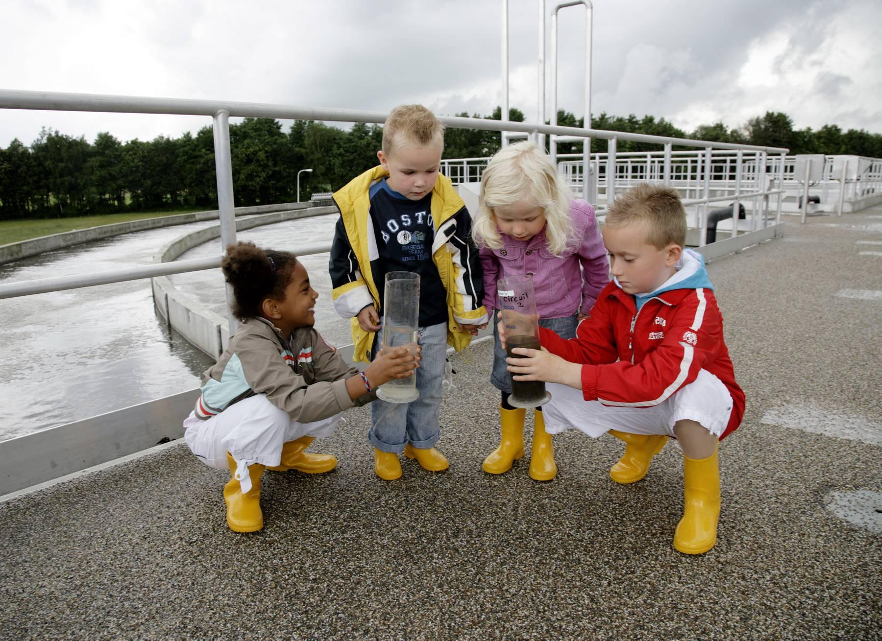 Kinderen met watermonsters op rioolwaterzuiveringsinstallatie