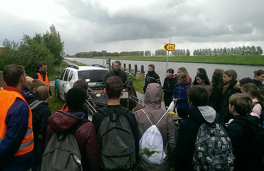 Leerlingen luisteren naar een waterschapper tijdens de Geoweek in waterschap Noorderzijlvest