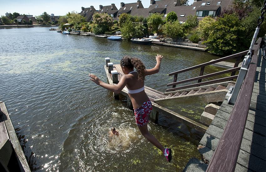 Kinderen duiken van een ophaalbrug over de Broekwegwetering nabij de Fregatwerf in Zoetermeer.
