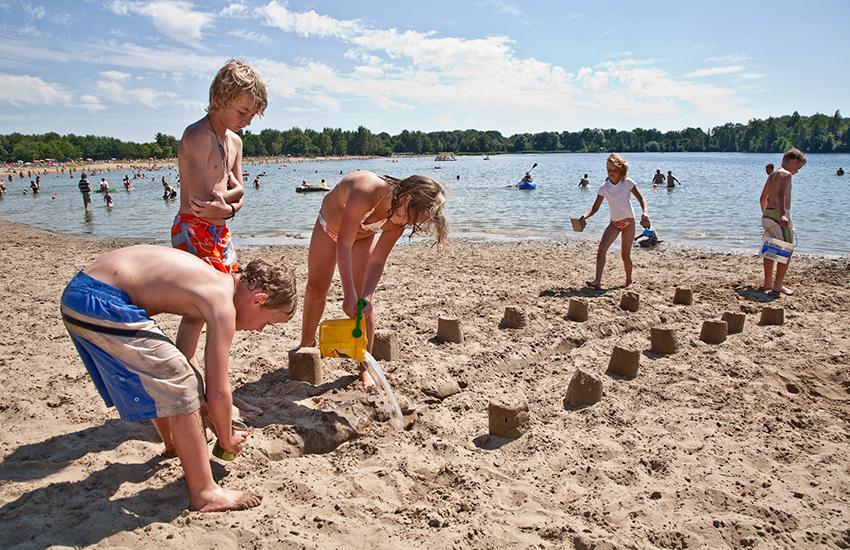 Kinderen spelen met water bij de recreatieplas 't Hilgelo bij Winterswijk.