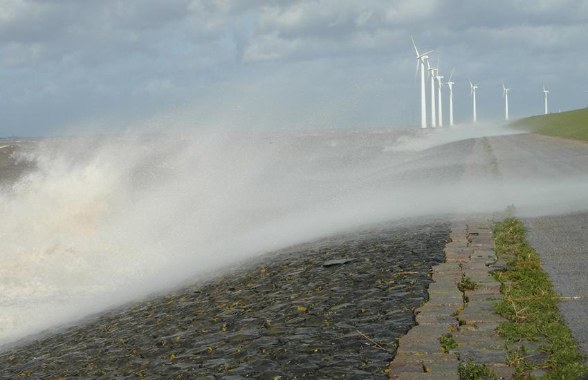Westerstorm stuwt water over de zeedijk