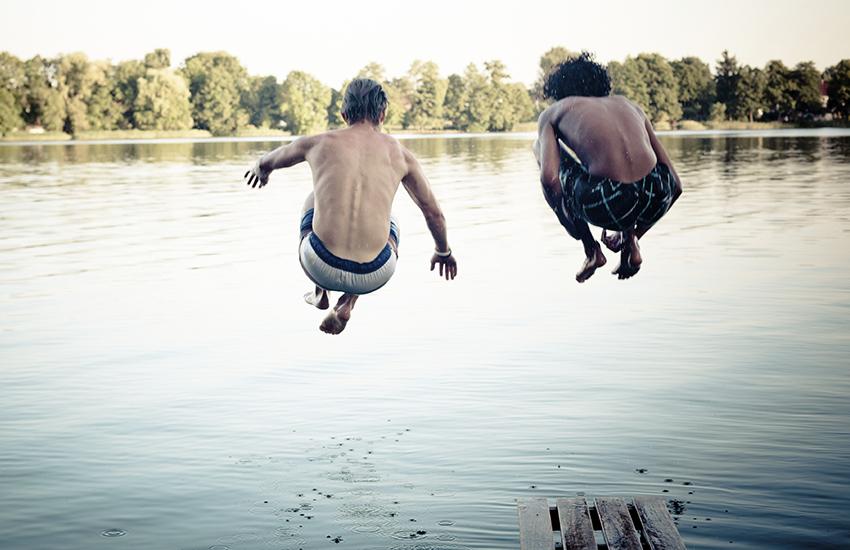 Jongens die in het water springen