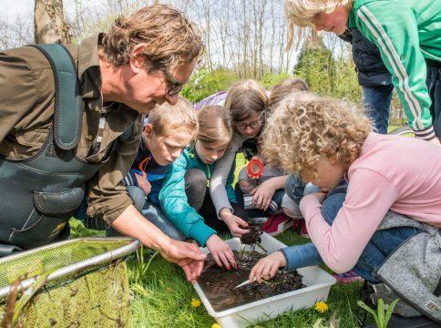 Waterschapper Peter van Duijnhoven laat kinderen een bak met modder zien
