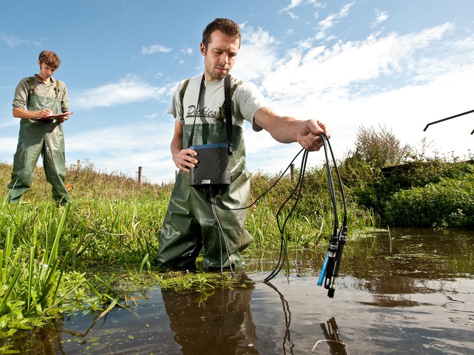 waterkwaliteit wordt in sloot gemeten door man met apparatuur